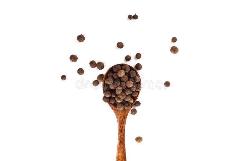 Allspice перца на деревянной ложке изолированной на белой предпосылке Ямайский болгарский перец r стоковое фото rf