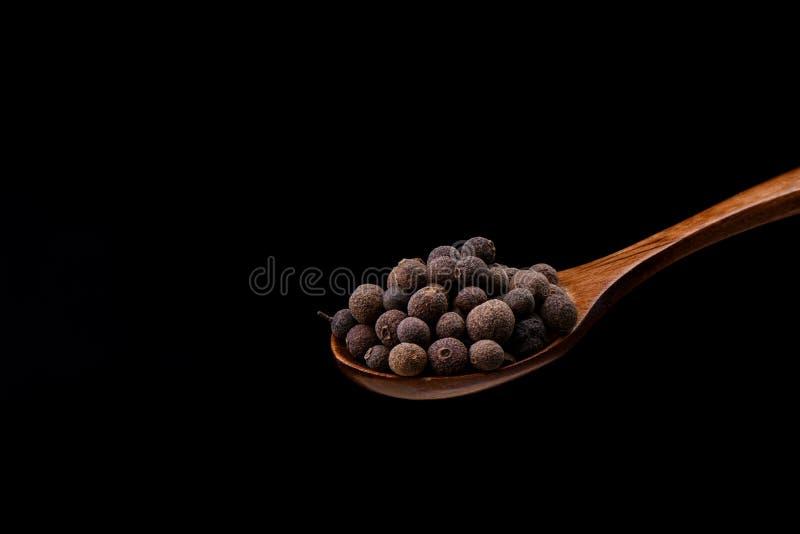 Allspice перца на деревянной ложке над черной предпосылкой Ямайский болгарский перец стоковое фото
