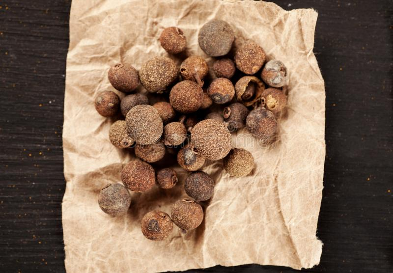 Allspice on a piece of wrinkled paper top view royalty free stock image