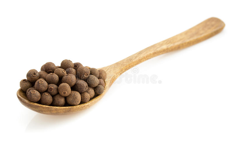 Allspice in spoon on white. Allspice in spoon isolated on white background royalty free stock image