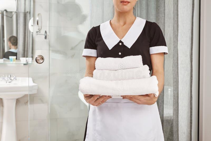 Allt är nytt och rent Kantjusterad stående av housecleaner i den enhetliga innehavpacken för hembiträde av vita handdukar anställ arkivbild