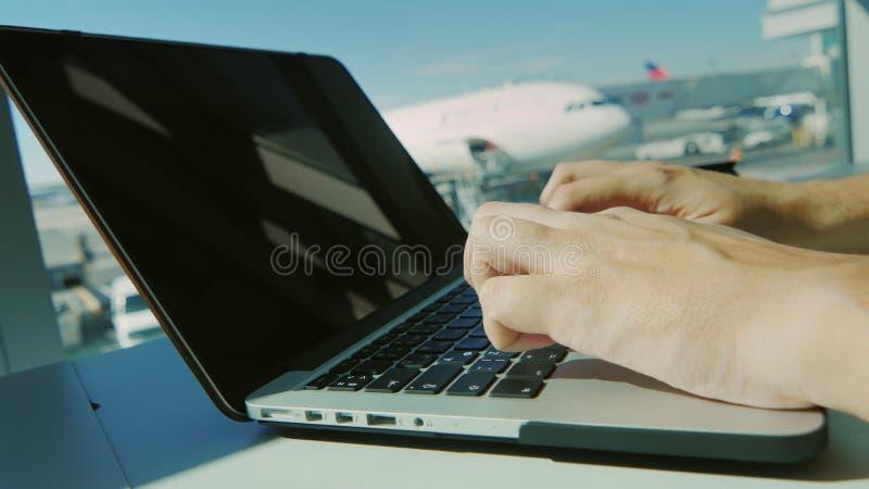 Alltid förbindelse Man maskinskrivningtext på bärbara datorn mot fönsterflygplatsen arkivbilder