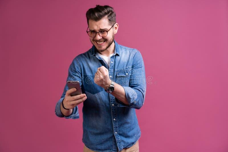 Alltid i handlag Le den unga mannen som rymmer den smarta telefonen och att se den Stående av en lycklig man som använder mobilte arkivfoto