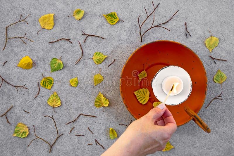 Allumage d'une bougie pour l'humeur confortable d'automne photographie stock