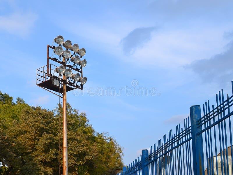 Allumage du mât avec les projecteurs puissants au-dessus du stade contre l'espace de copie de ciel bleu image libre de droits