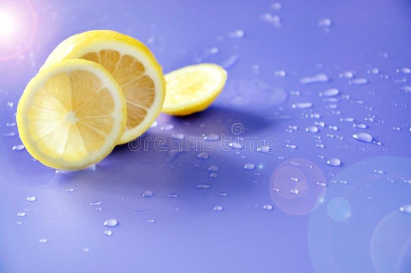 Allumage sur le citron frais avec la baisse de l'eau sur le fond images stock