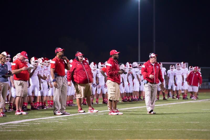 Allume vendredi soir des entraîneurs de football américain de lycée sur la ligne de touche image libre de droits