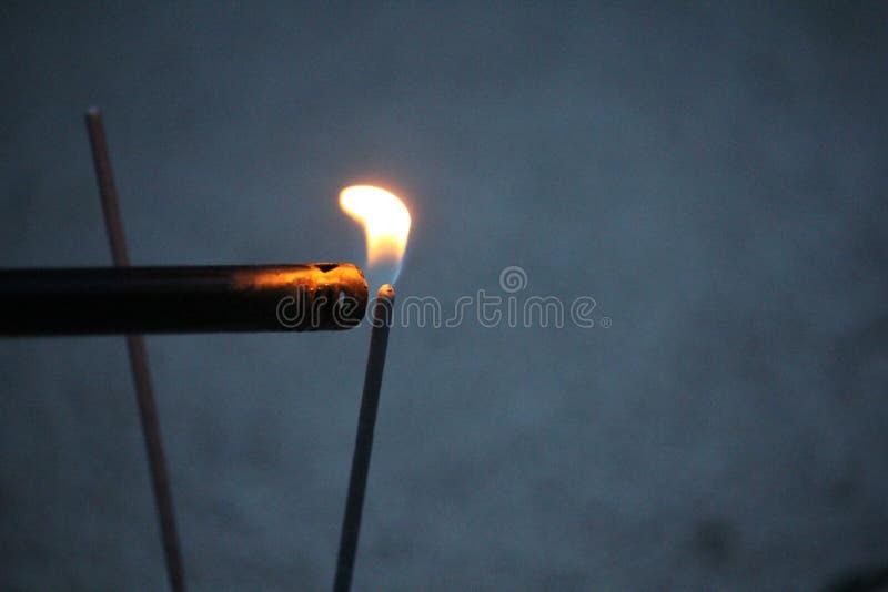 Allumeur avec la flamme sur un cierge magique image stock