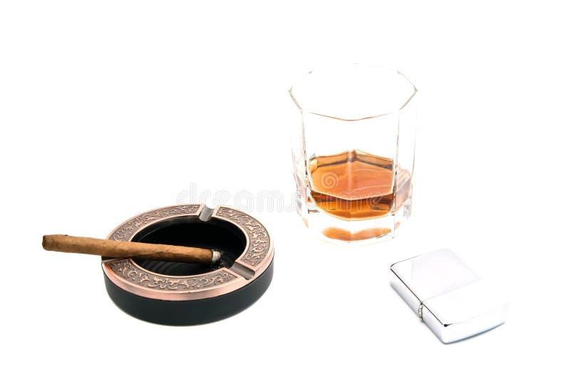 Allumeur, cigarillo dans le cendrier et alcool photo stock