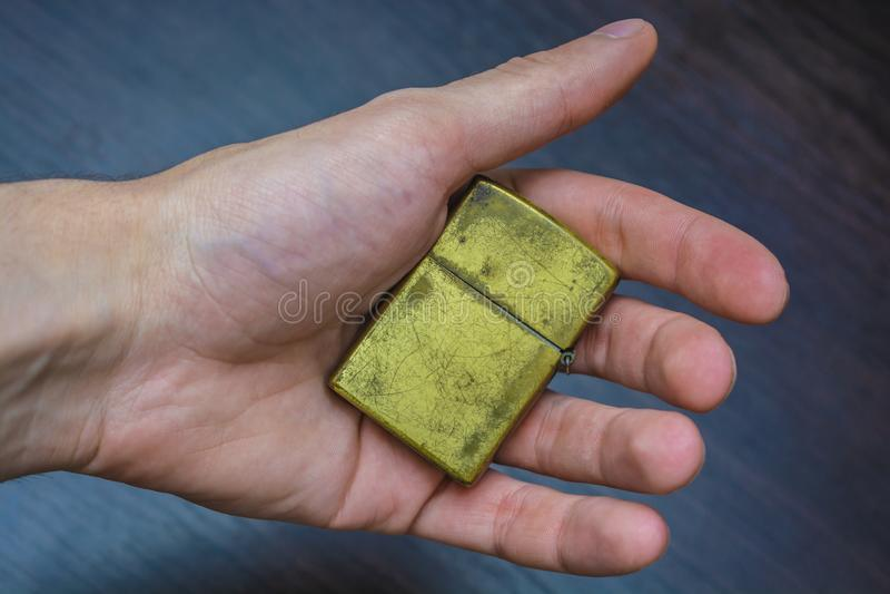 Allumeur d'or tenu dans la main de pliage photo stock