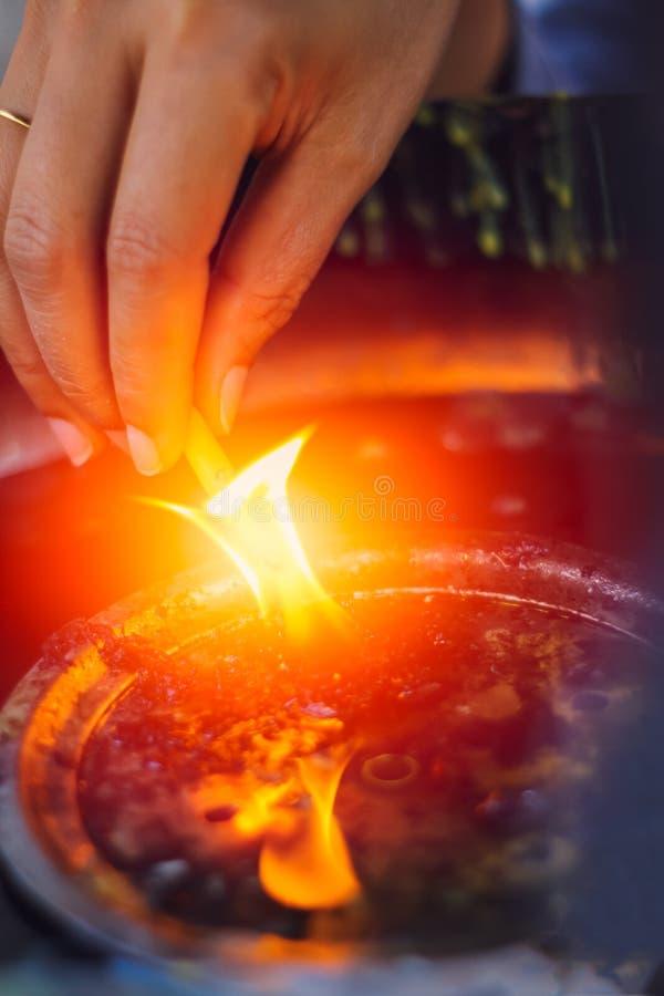 Allumez la bougie, bougie de prise de main mettent le feu de la lampe à pétrole images stock