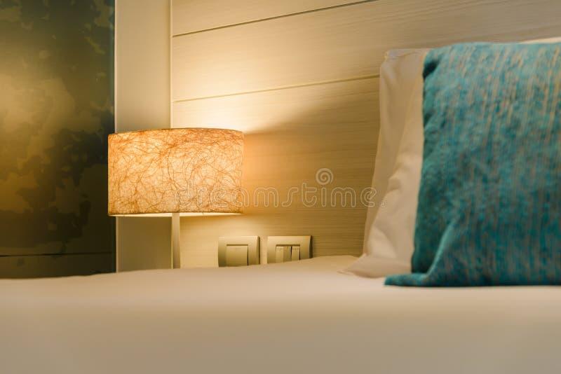 Allumez la lampe de chevet sur la table de chevet dans la chambre à coucher image stock