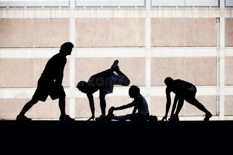 Allungamento dei corridori delle donne e degli uomini. immagini stock libere da diritti