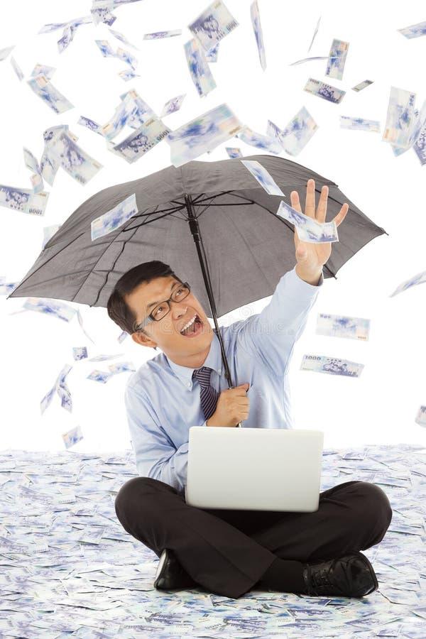 Allungamento felice dell'uomo di affari la sua mano per afferrare soldi immagini stock libere da diritti