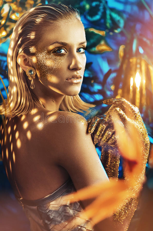 Alluring blond woman with golden dust on her body royalty free stock photography