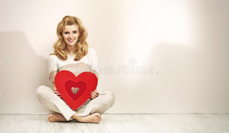 Alluring blonde girl holding red heart royalty free stock photography