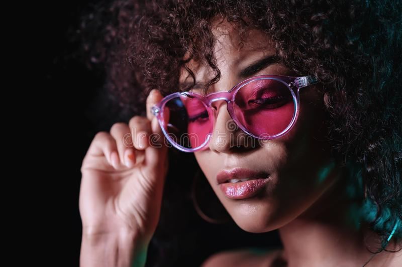 Alluring unusual girl with curly afro hair corrects her glasses. Sexy woman with perfect makeup looking at camera and royalty free stock photo