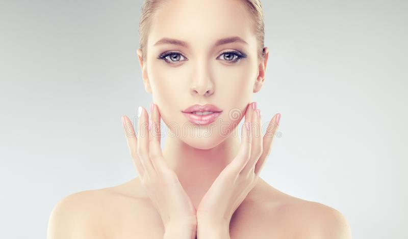 Alluring woman with clean fresh skin is touching the face tenderly. stock photo