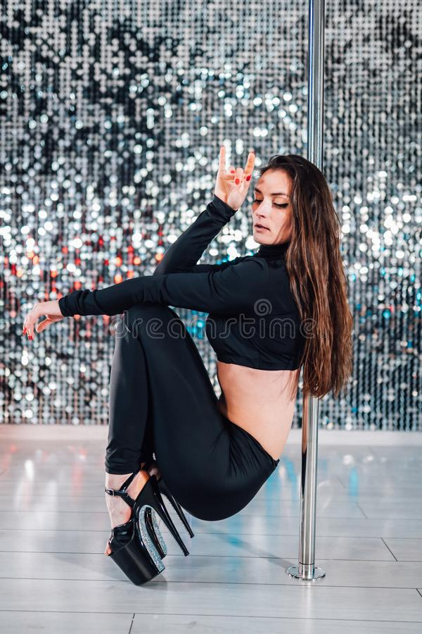 Alluring woman with long hair posing with pylon on shining wall background. Pole-dance, sexy, temptation concept. stock photography