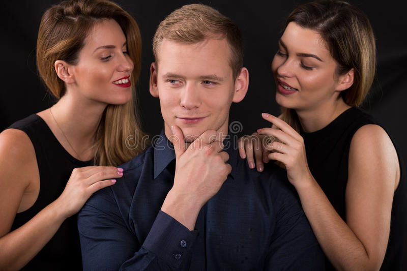 Alluring women seducing narcissistic man. Picture of alluring women seducing narcissistic man stock photos