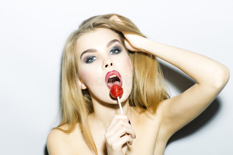 Alluring young blonde woman portrait with sugar candy. Alluring young blonde woman portrait with bright make up looking forward holding and licking round red stock photo