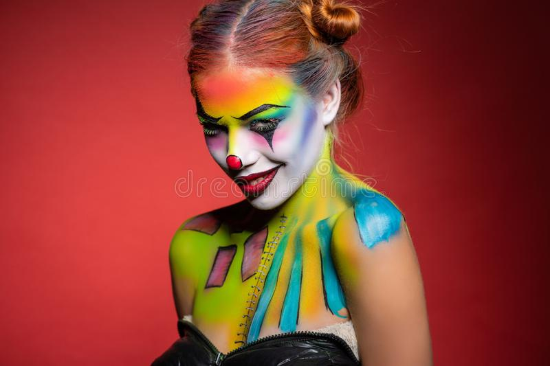 Alluring young woman with a aqua makeup clown. Posing in the studio on a red background stock photo
