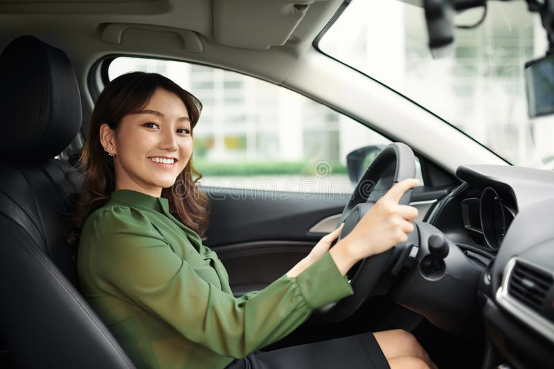 Alluring young woman driving the car and smiling royalty free stock images