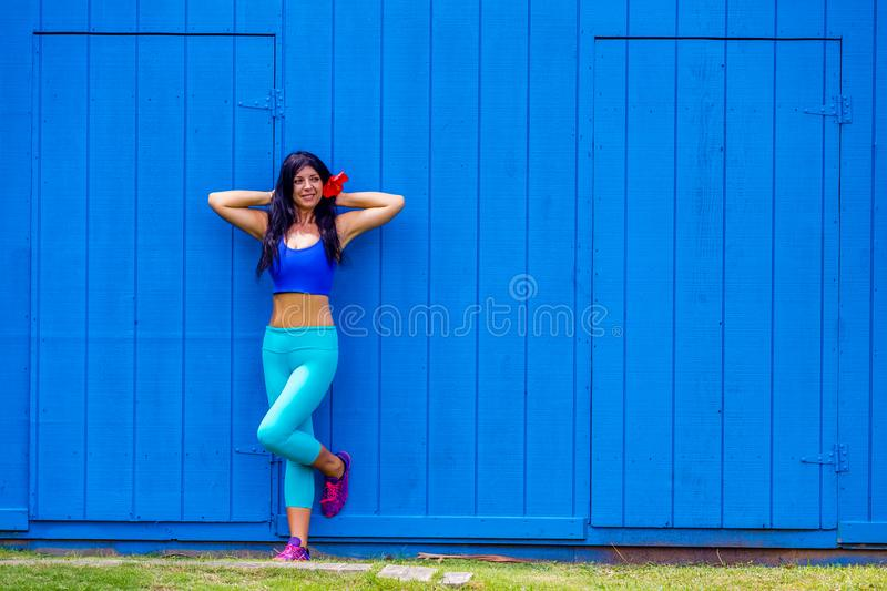 Alluring young woman with a hibiscus in her hair. Posing leaning against a bright colorful blue wooden wall in Oahu, Hawaii with a happy smile stock photos