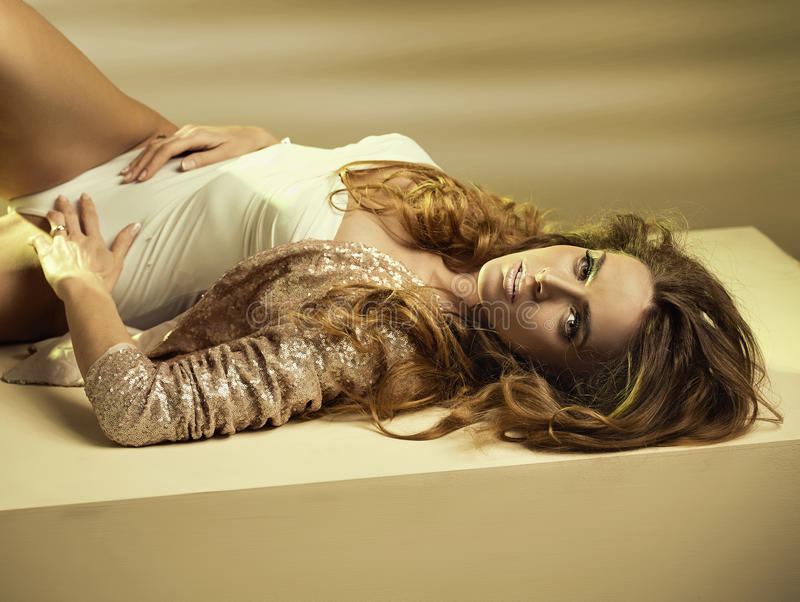 Alluring Young Woman Lying Down On The Floor Royalty Free Stock Images