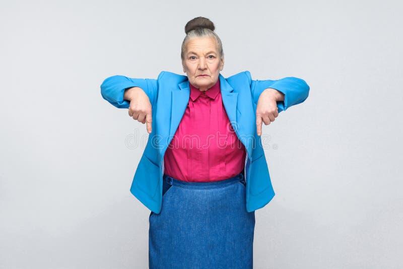 Allvarlig åldrig kvinna som pekar fingrar på kopieringsutrymme royaltyfri bild