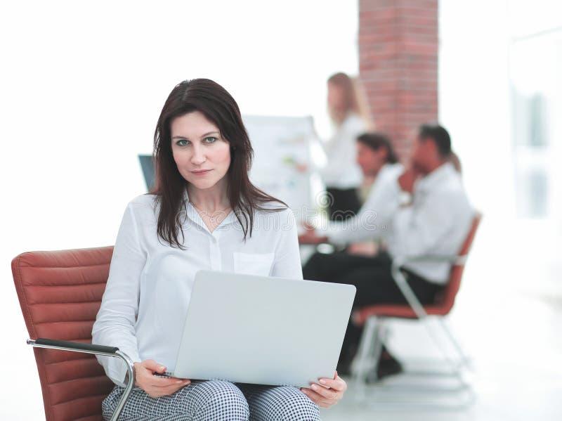 Allvarlig affärskvinna med bärbar datorsammanträde i lobbyen av kontoret royaltyfri bild