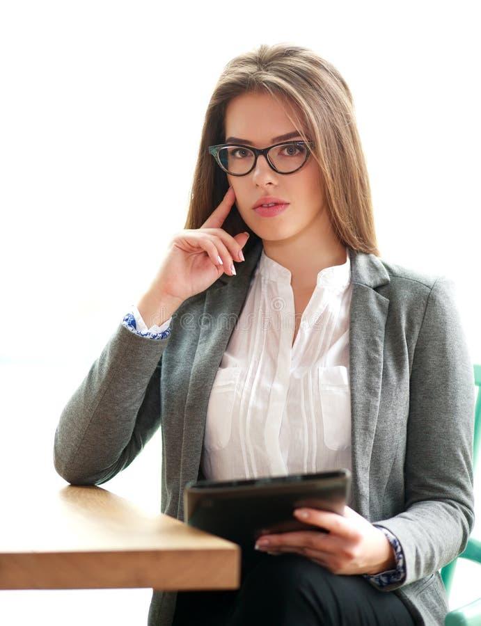 Allvarlig affärskvinna med bärbara datorn i regeringsställning på vit arkivbild