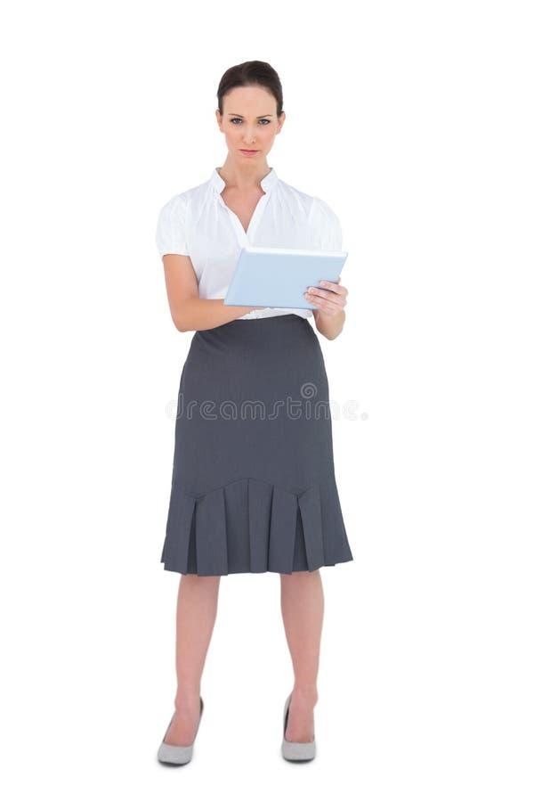 Allvarlig affärskvinna som använder minnestavladatoren royaltyfri bild