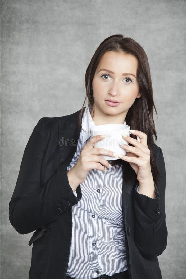 Allvarlig affärskvinna som dricker kaffe royaltyfri bild