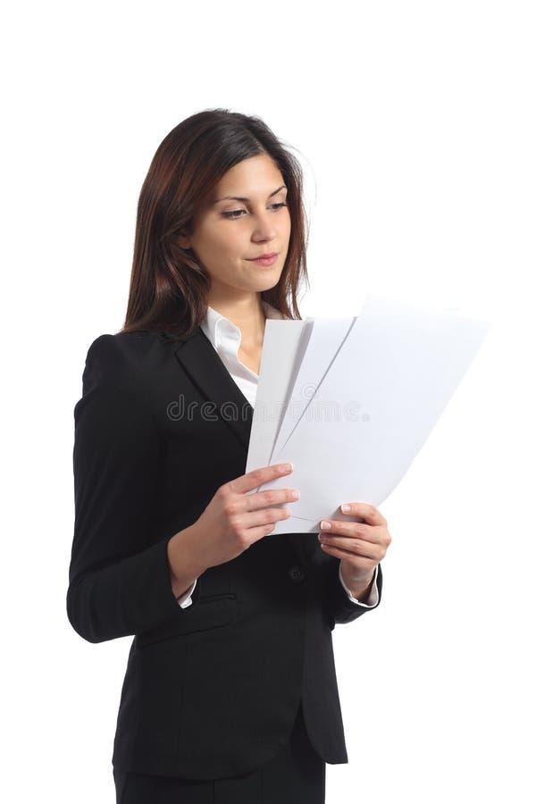 Allvarlig affärskvinna som läser en rapport fotografering för bildbyråer