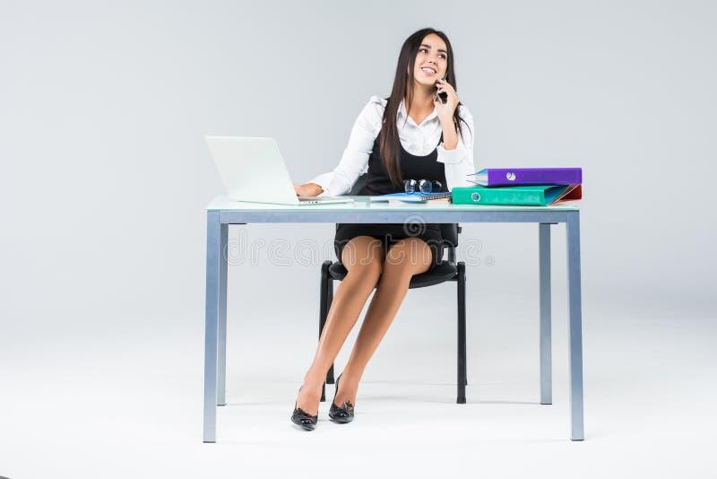 Allvarlig affärskvinna som ser bärbar datorskärmen, medan tala på mobiltelefonen på hennes arbetsskrivbord som isoleras på vit ba arkivbild