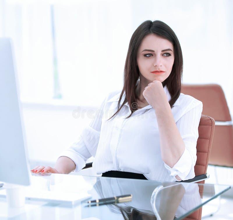 Allvarlig affärskvinna som sitter på skrivbordet i kontoret royaltyfria bilder