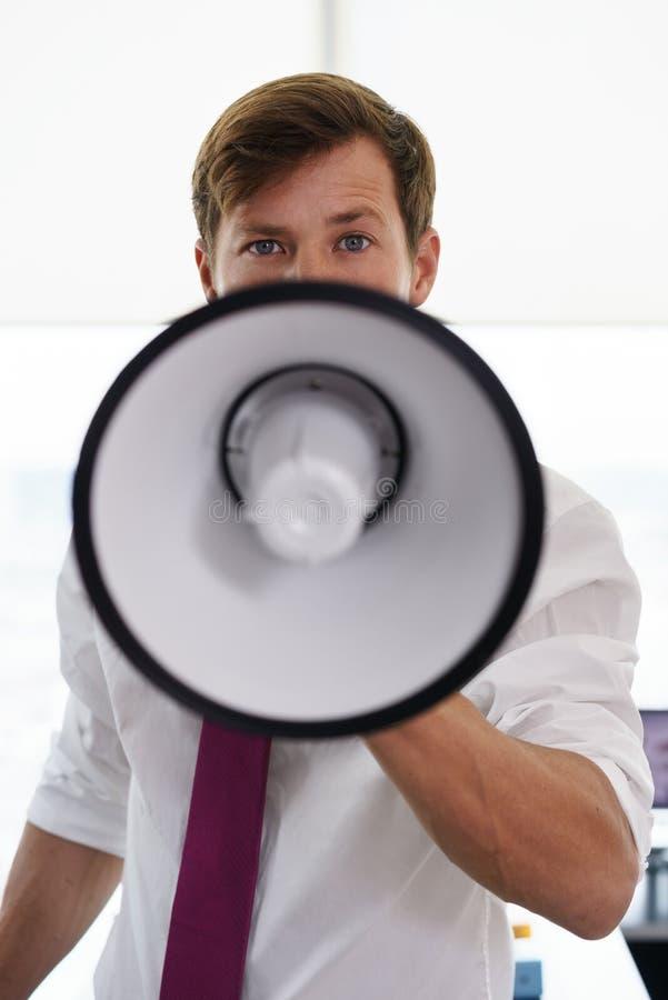 Allvarlig affärsman för stående med megafonen i regeringsställning royaltyfri bild