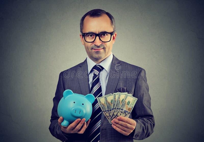 Allvarlig affärsman i exponeringsglas med spargris- och dollarkassasedlar arkivbild