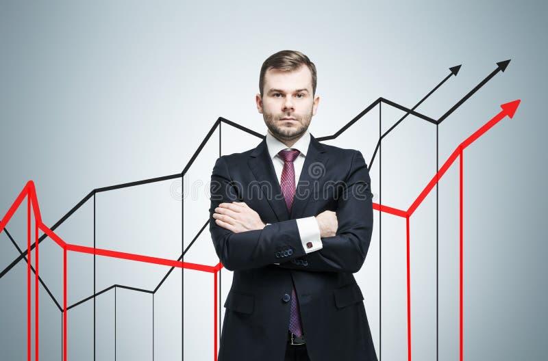 Allvarlig affärsman och tre växande grafer på den gråa väggen royaltyfri foto