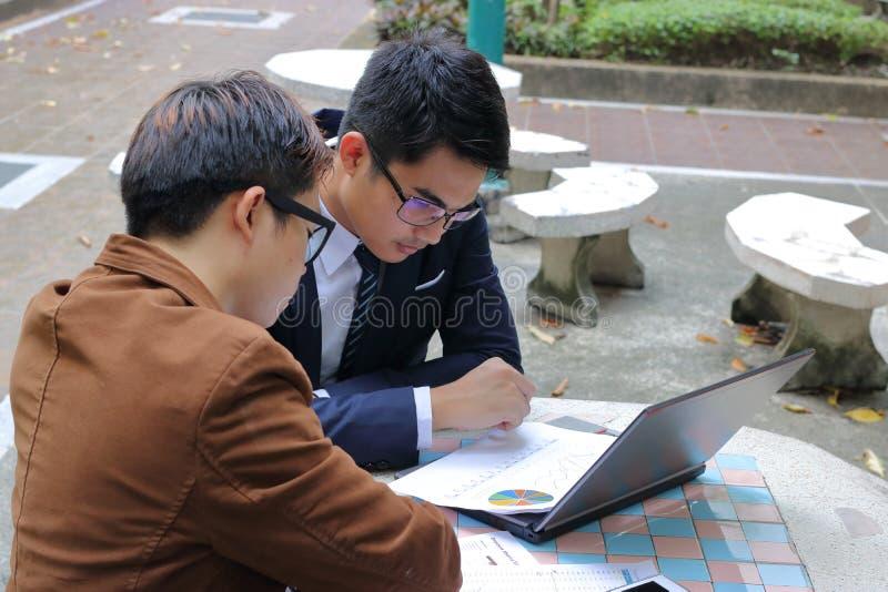 Allvarlig affärsman som analyserar data under möte på offentligt utomhus- royaltyfria foton