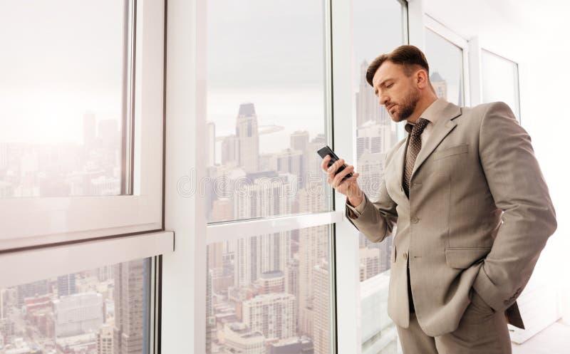 Allvarlig affärsman som använder smartphonen arkivfoto
