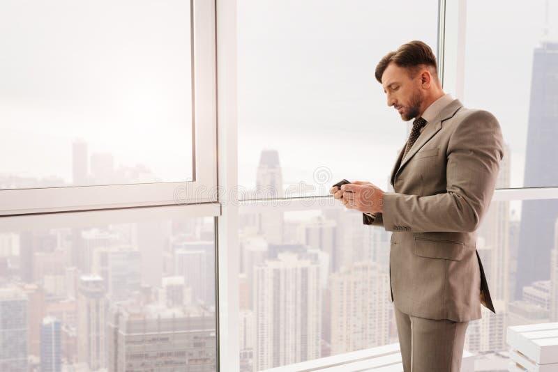 Allvarlig affärsman som använder smartphonen i hans kontor fotografering för bildbyråer