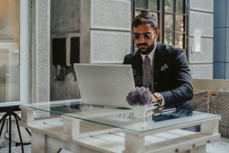 Allvarlig affärsman som arbetar på en bärbar dator i ett kafé arkivfoto