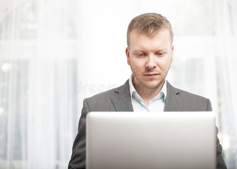 Allvarlig affärsman som arbetar på hans bärbar datordator royaltyfria foton