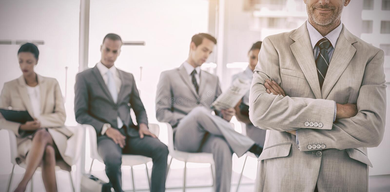 Allvarlig affärsman som framme står av affärsfolk arkivbild