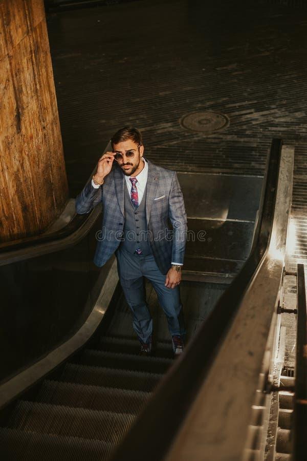 Allvarlig affärsman som går upp på rulltrappan, medan rymma sjungit royaltyfria bilder