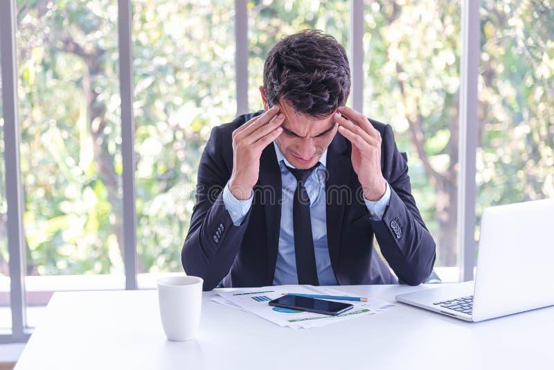 Allvarlig affärsman som sitter i mötesrum med papper, grafen, bärbara datorn, mobiltelefonen och koppen kaffe på tabellen fotografering för bildbyråer