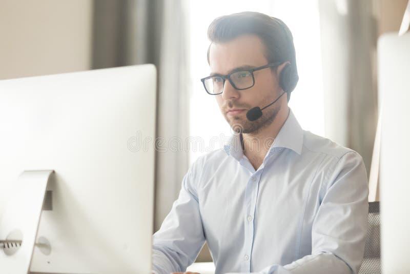 Allvarlig affärsman som talar med hörlurar med mikrofon på datoren som gör konferenssamtal fotografering för bildbyråer