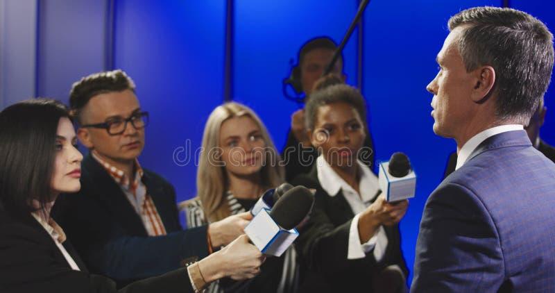 Allvarlig affärsman som talar till massmediarepresentanter royaltyfri bild